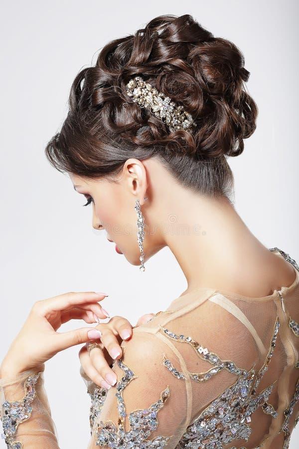 Elegância e chique. Morena bonita com penteado elegante. Luxo fotos de stock royalty free