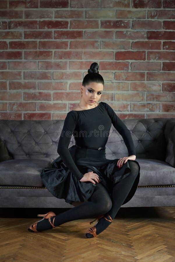 Eleganccy łacińscy kobieta tancerze w czerni ubierają pozować blisko kanapy obraz royalty free