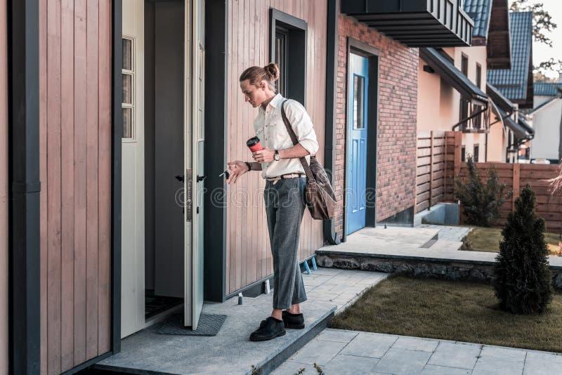 Eleganccy biznesmena mienia klucze podczas gdy wchodzić do jego dom po pracy zdjęcie stock