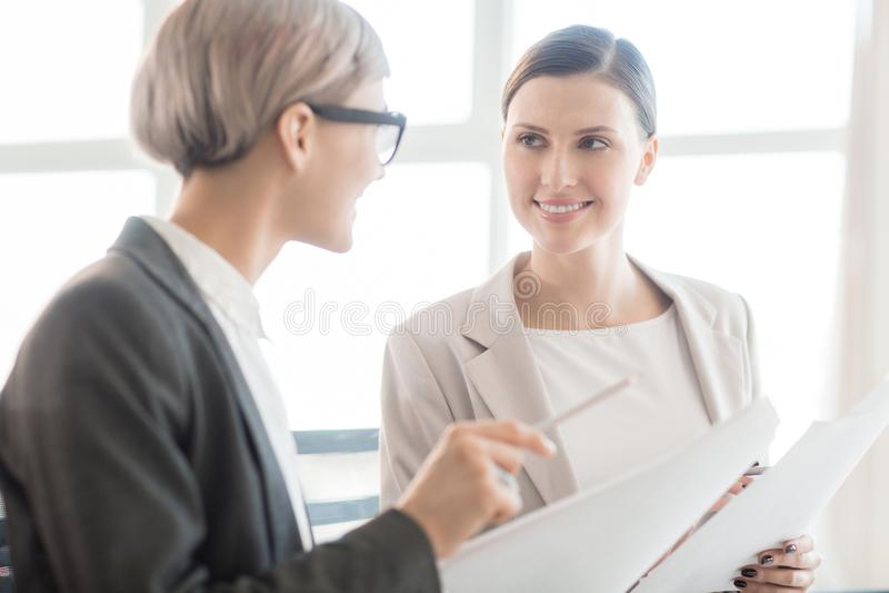 Eleganccy bizneswomany komunikuje z papierami zdjęcia stock