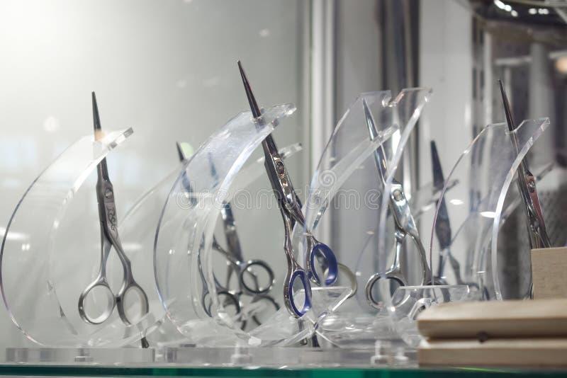 Eleganccy Fachowi fryzjerów męskich nożyce, Włosiany rozcięcie i wiotczenie nożyce w detalicznego sklepu szklanego okno pokazie,  zdjęcie stock