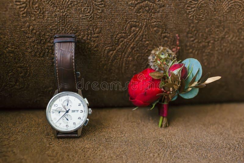 Eleganccy fornala ` s akcesoria na brown tle Boutonniere i wristwatches grafika zdjęcie royalty free