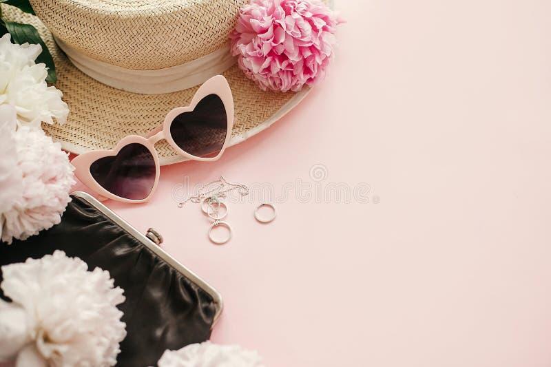 Eleganccy girly różowi retro okulary przeciwsłoneczni, peonie, biżuteria, kapelusz, kiesa na pastelowych menchiach tapetują z kop obrazy stock
