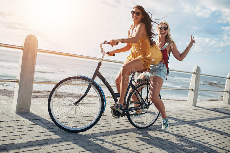 Eleganccy młodzi żeńscy przyjaciele na bicyklu zdjęcie stock