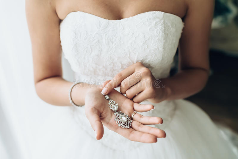 Eleganccy panny młodej mienia srebra kolczyki Ofert ręki z biżuterią fotografia stock