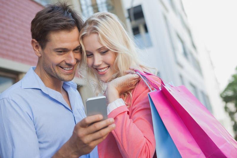 Eleganccy potomstwa dobierają się patrzeć smartphone mienia torba na zakupy zdjęcia stock