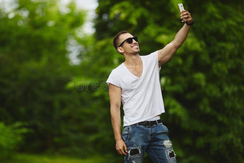 Eleganccy przystojni młodzi sportowi mężczyzna w białych cajgach i koszulce, robią selfie na jego smartphone obraz royalty free