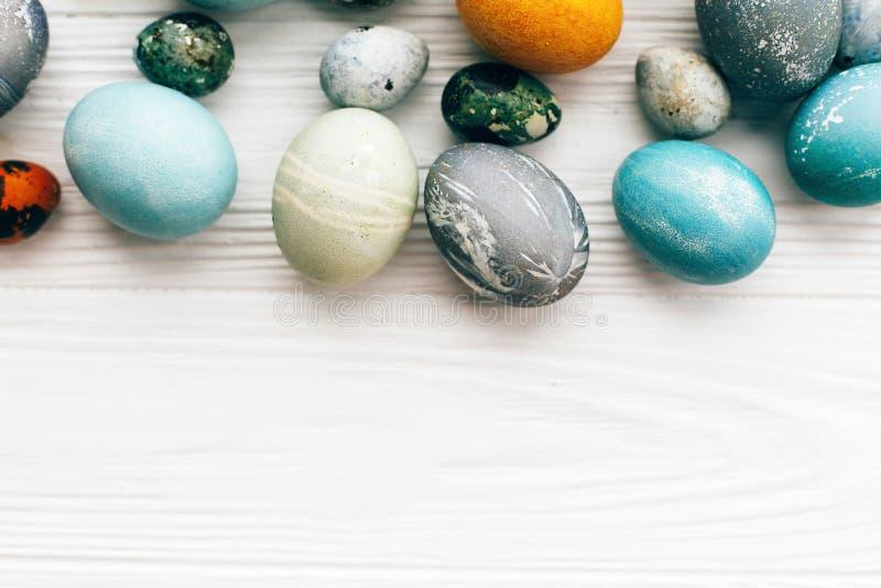 Eleganccy Wielkanocni jajka graniczą na białym drewnianym tle, kopii przestrzeń Nowożytni Easter jajka malowali z naturalnym barw obraz royalty free