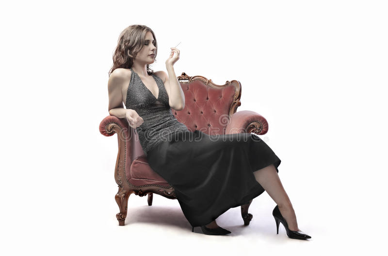 Elegance. Beautiful woman sitting on an armchair and smoking a cigarette royalty free stock photography