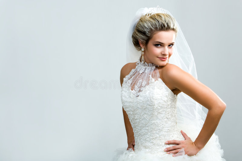 Elegance. Portrait of young female in wedlock keeping her hands on waist and looking at camera from aside royalty free stock images