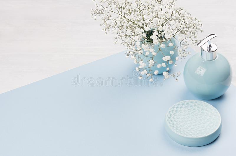 Elegance ceramic glossy round bowls as bathroom accessories in pastel blue color with white flowers closeup on wood board. stock photo