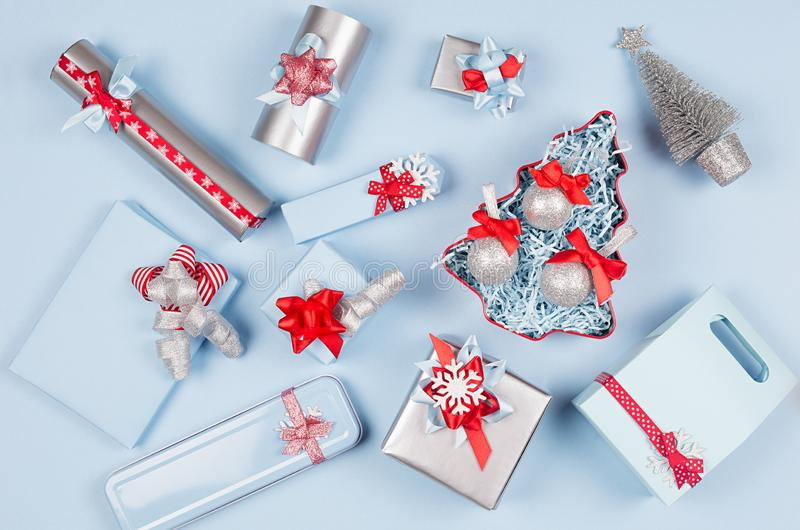 Elegance christmas silver metallic and blue paper gift boxes with red silk ribbons, decorations on pastel blue background. Elegance christmas silver metallic royalty free stock photos