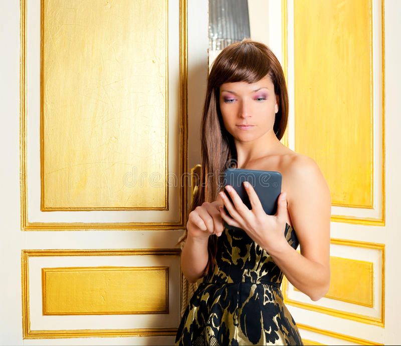 Elegance fashion woman reading ebook. Tablet in golden door royalty free stock photos
