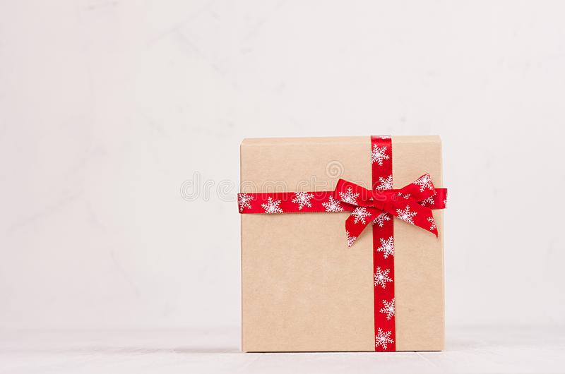 Elegance festive a gift box of kraft paper with a red ribbon and bow on white wood board with copy space. stock photography