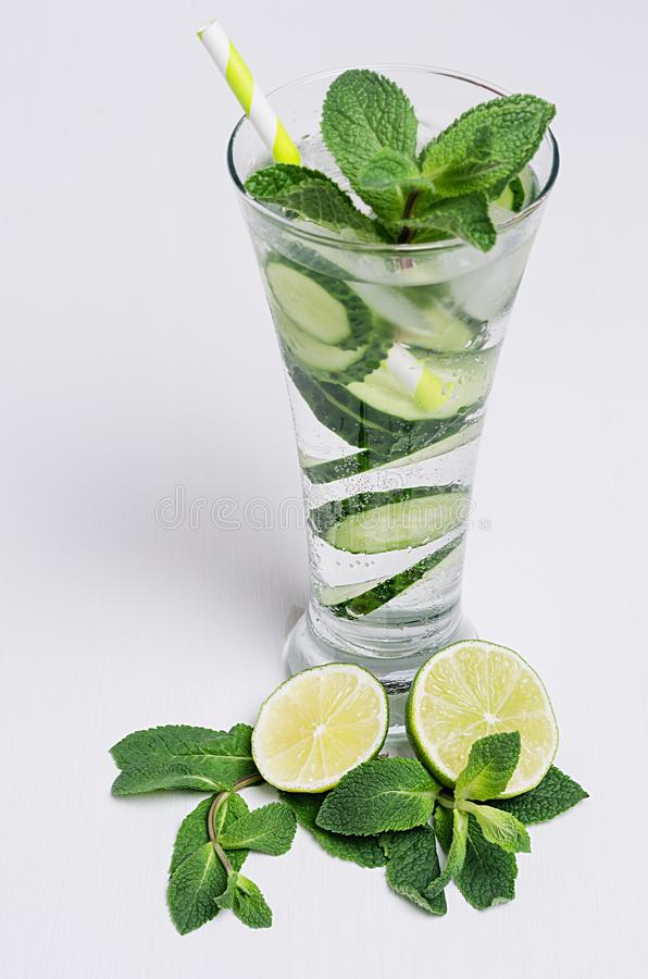 Elegance high glass with cold natural refreshing cocktail with slices cucumber, lime, mint, ice, straw on white wood plank. royalty free stock photos