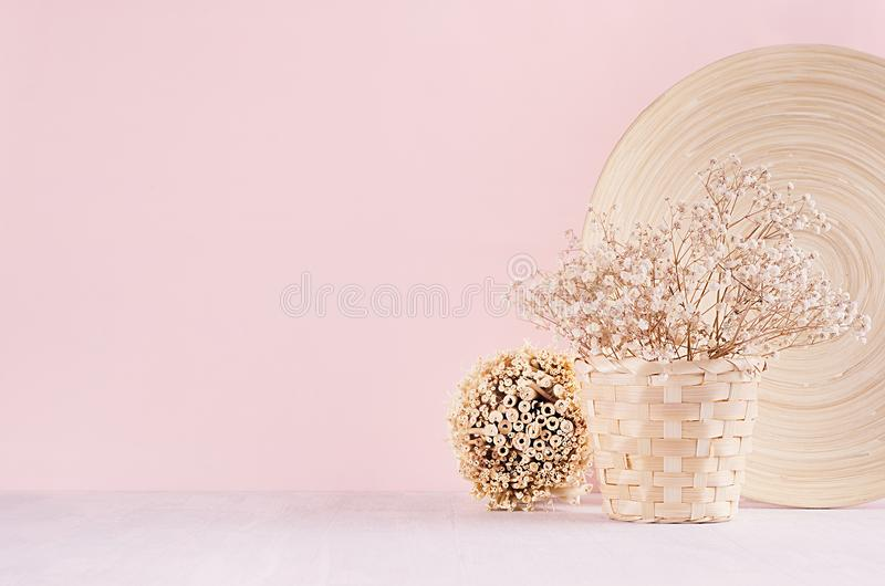 Elegance home eco decor - white dried flowers bouquet in basket with decorative plate, bunch sticks on fashion pink background. royalty free stock image