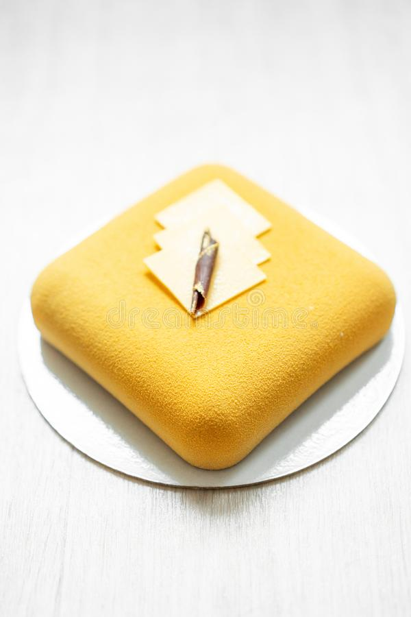 Elegance square velour mousse cake. nut and fruit filling inside. Contemporary yellow pie. selective focus. white table. royalty free stock photos