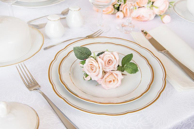 Elegance table setting. Beautifully decorated table with white plates, glasses, cutlery and flowers on luxurious tablecloths royalty free stock photos