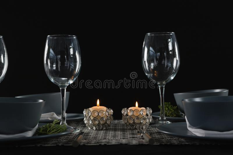 Elegance table setting with empty wine glasses and lit candle. On table stock photo