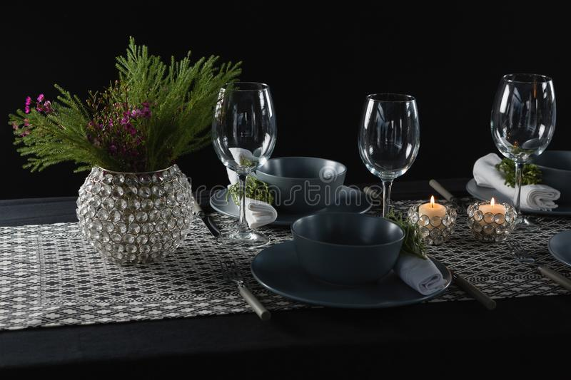 Elegance table setting with empty wine glasses and lit candle. On table stock image