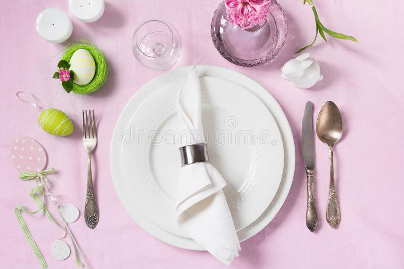 Elegance table setting spring pink flowers on with pink linen tablecloth. Easter romantic dinner. Top view. royalty free stock photo