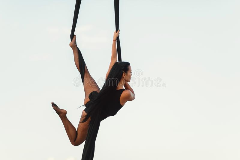 Elegance young beautiful woman dance with aerial silk on a sky background. Fly yoga sport stock photography