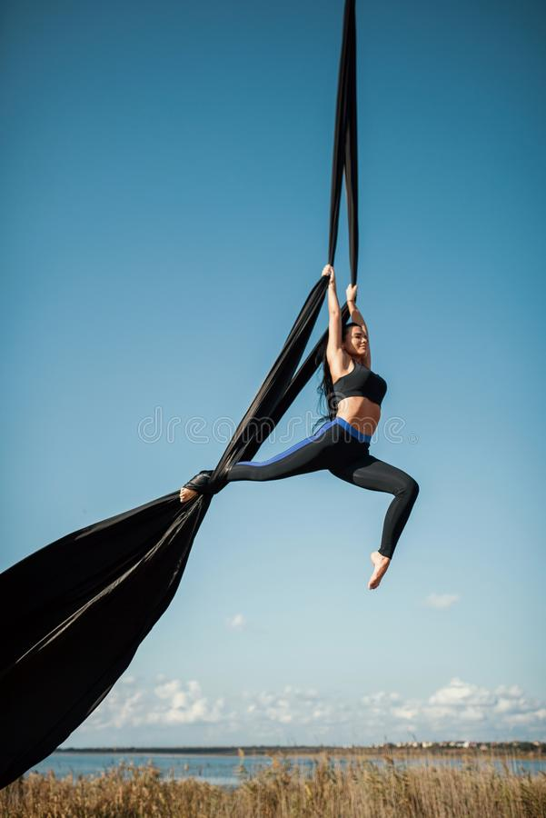 Elegance young beautiful woman dance with aerial silk on a sky background. Fly yoga sport royalty free stock photography