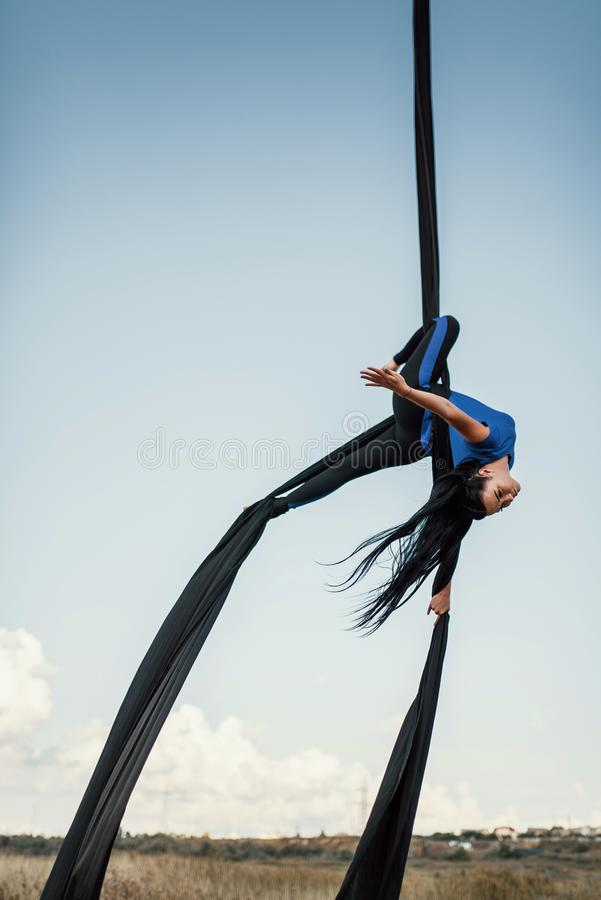 Elegance young beautiful woman dance with aerial silk on a sky background. Fly yoga sport stock image