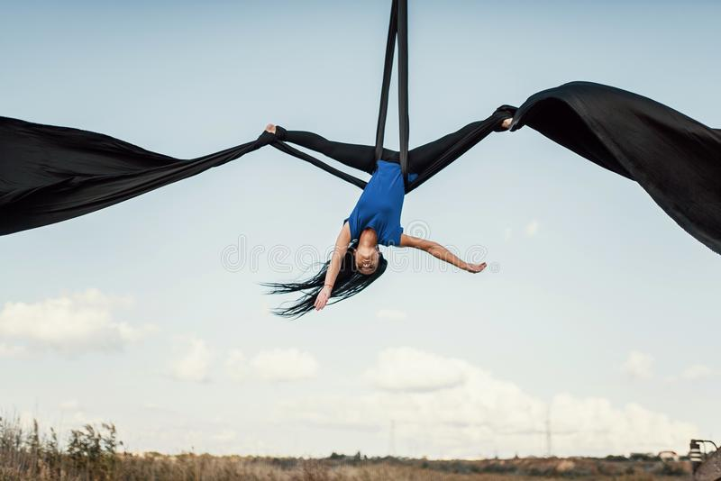 Elegance young beautiful woman dance with aerial silk on a sky background. Fly yoga sport royalty free stock photos