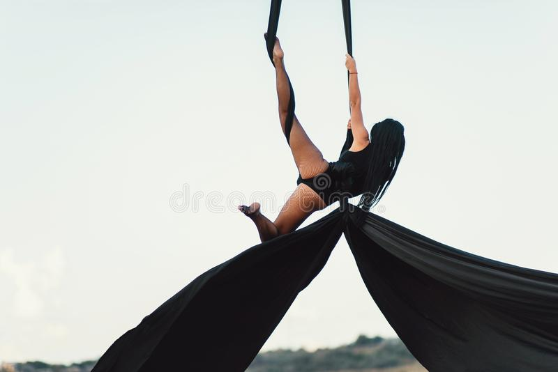 Elegance young beautiful woman dance with aerial silk on a sky background. Fly yoga sport stock images