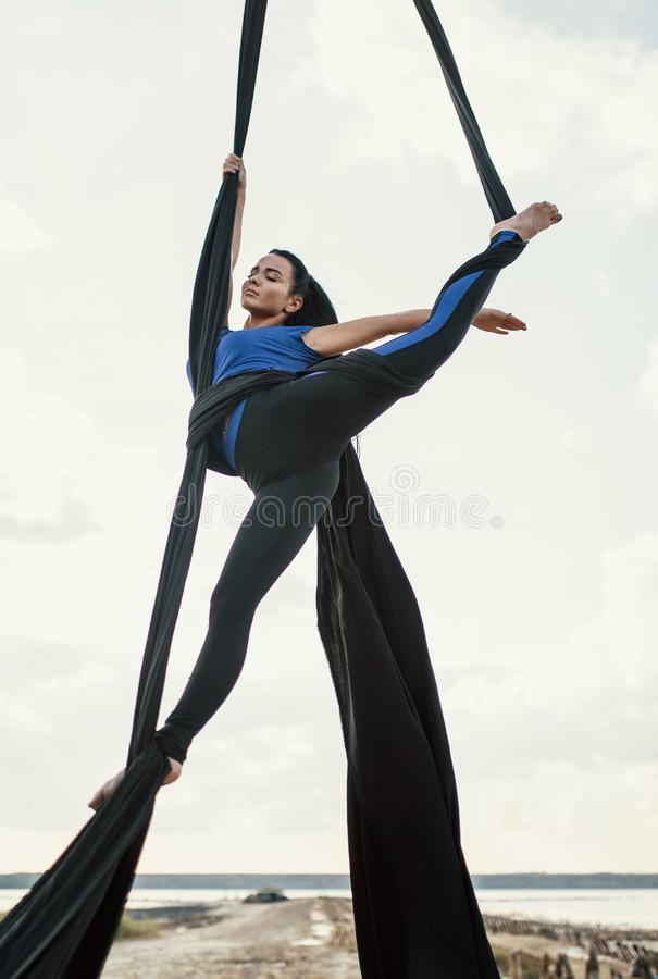 Elegance young beautiful woman dance with aerial silk on a sky background. Fly yoga sport stock photo