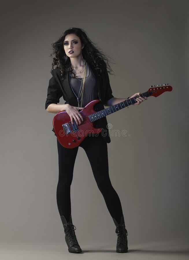 Elegancia atractiva del eje de balancín en negro con la guitarra roja imágenes de archivo libres de regalías
