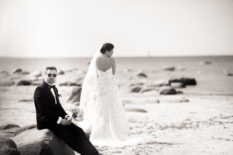 Elegancka ?lub pary pozycja na dennym brzeg Nowo?e?cy chodz? morzem czarny white zdjęcie stock