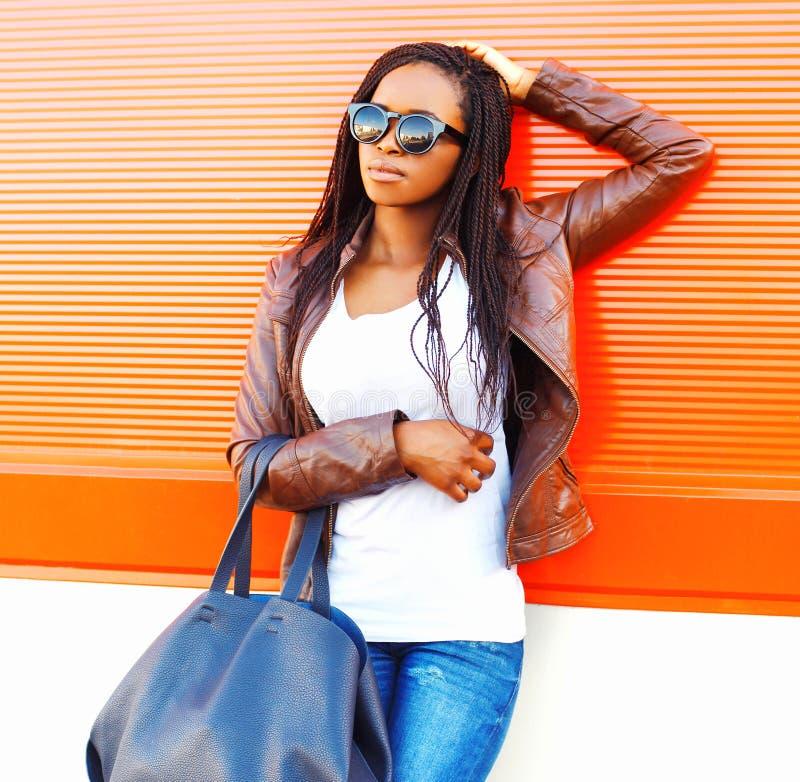 Elegancka afrykańska kobieta w okularach przeciwsłonecznych z torbą pozuje przy miastem zdjęcie stock