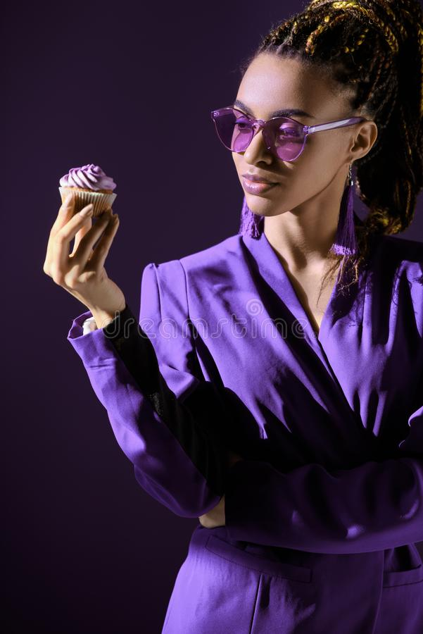 Elegancka amerykanin afrykańskiego pochodzenia dziewczyna patrzeje babeczkę w ultrafioletowej kurtce i okularach przeciwsłoneczny fotografia stock