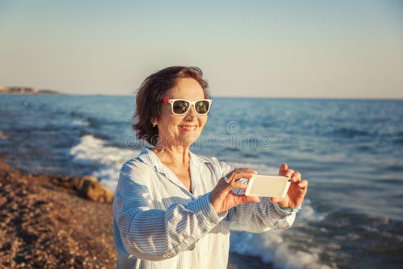 Elegancka atrakcyjna dojrzała kobieta 50-60 robi fotografiom mobilny pho fotografia royalty free