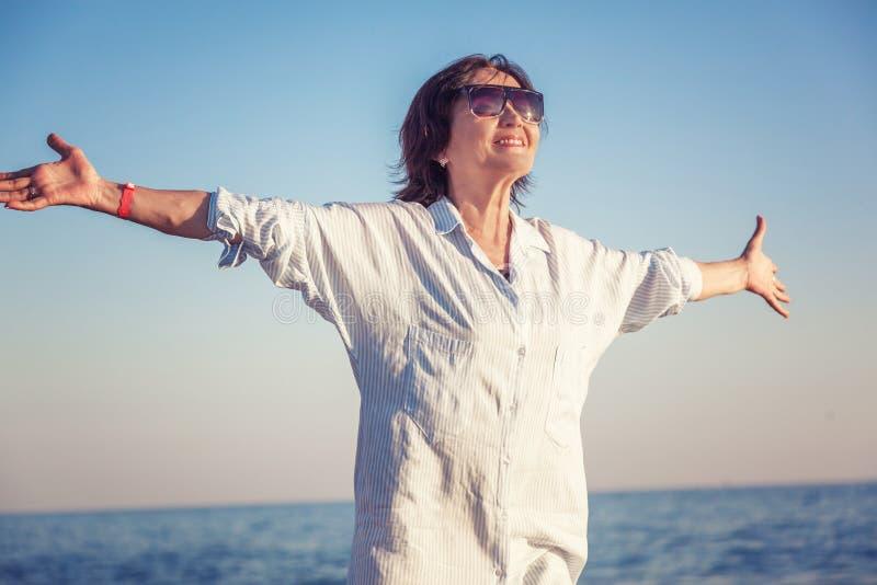 Elegancka atrakcyjna dojrzała kobieta 50-60 z otwartymi rękami na morzach zdjęcia stock