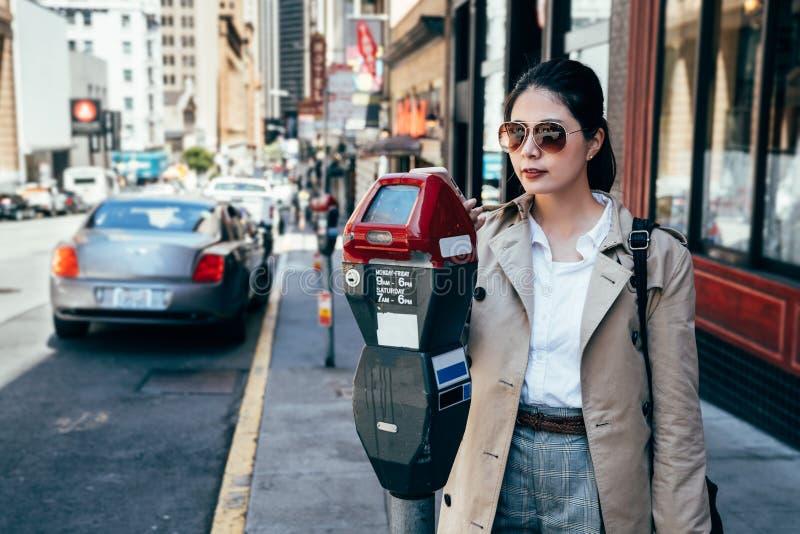 Elegancka biurowa dama używa parking metr na ulicie obrazy stock