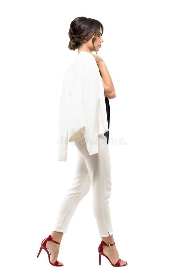 Elegancka biznesowa kobieta w białym kostiumu odprowadzeniu i przewożenie kurtka nad ramieniem Boczny widok fotografia royalty free
