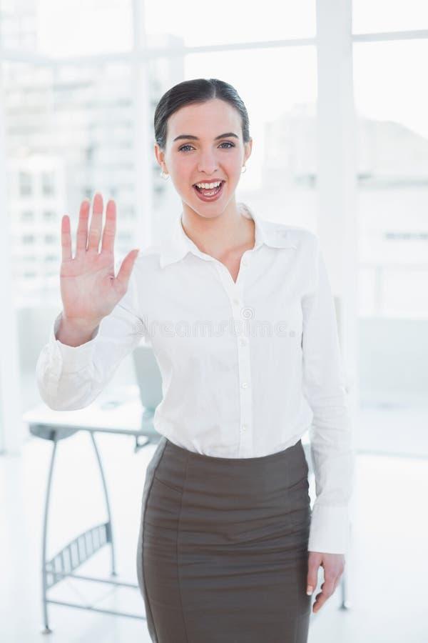 Elegancka bizneswomanu falowania ręka w biurze zdjęcia stock