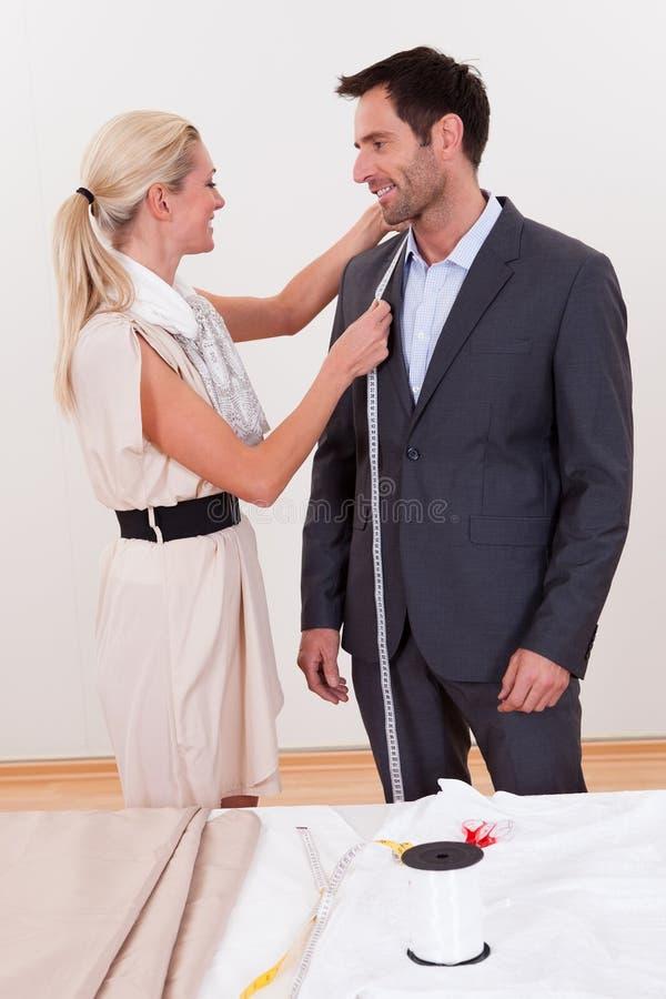 Szwaczka mierzy mężczyzna dla kostiumu fotografia royalty free