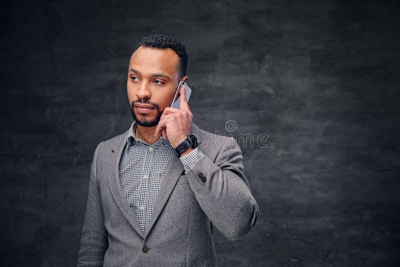 Elegancka brodata czarna samiec w popielatym kostiumu opowiada na mądrze telefonie zdjęcia royalty free