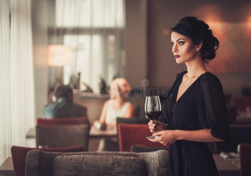 Elegancka brunetki dama w czarnej wieczór sukni z szkłem czerwień w fotografia stock