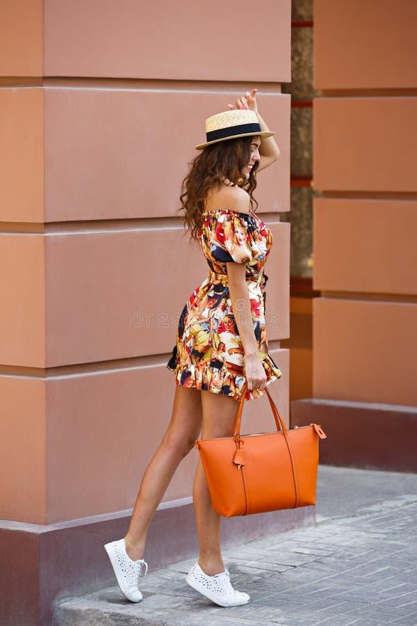Elegancka brunetki dziewczyna ubiera? w kr?tkich barwi?cych smokingowego i kapeluszowego mienia torby pomara?czowych spacerach w  zdjęcia stock