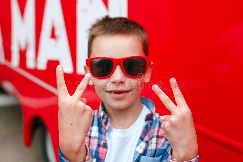 Elegancka chłopiec w czerwonych okularach przeciwsłonecznych pokazuje pokoju signoutdoor zdjęcia royalty free