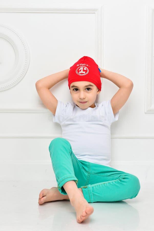 Elegancka chłopiec w czerwonym kapeluszu i cajgach na białym tle w studiu Modni dzieci fotografia royalty free