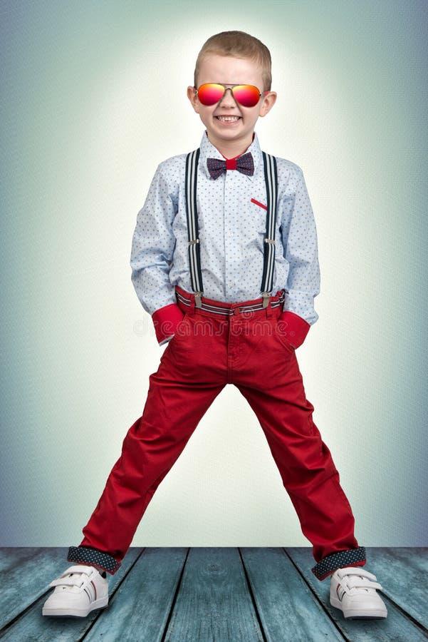 Elegancka chłopiec w modnych ubraniach i okularach przeciwsłonecznych od słońca Dziecka ` s moda fotografia royalty free