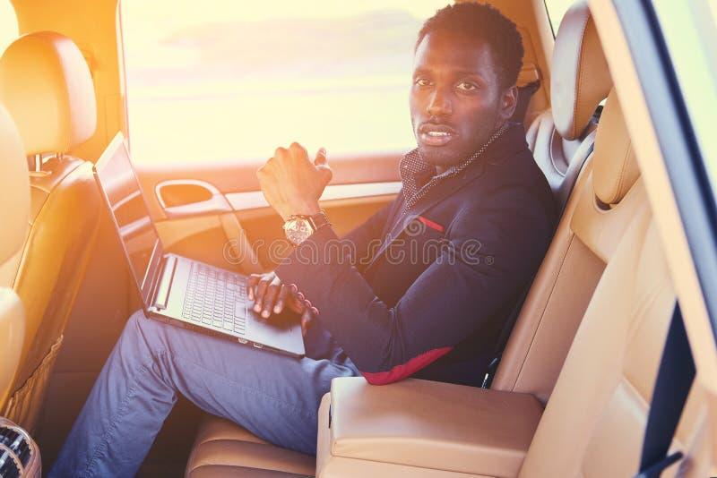 Elegancka Czarna samiec w samochodzie używać laptop zdjęcie royalty free