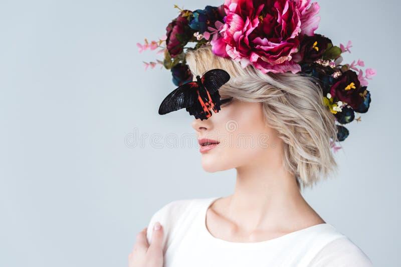 elegancka dziewczyna pozuje w kwiecistym wianku z pięknym żywym motylem na twarzy, zdjęcie stock