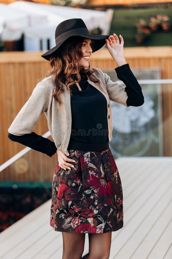 Elegancka dziewczyna ubiera? w czarnym turtleneck, be?owym przyl?dku, eleganckiej kr?tkiej sp?dnicie i czarnym kapeluszu z szerok zdjęcia stock